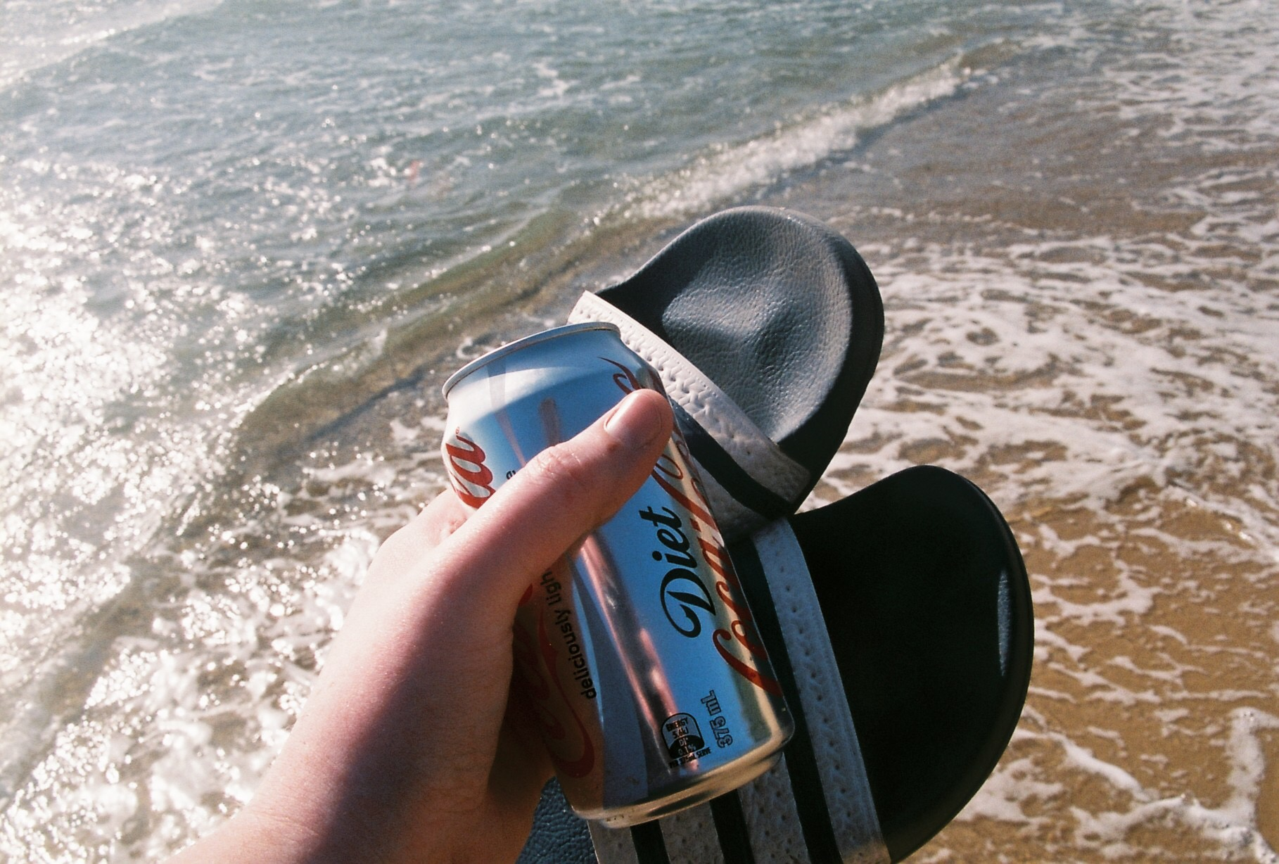 a hand holding a pair of slip-on slides and a can of diet coke in front of the ocean